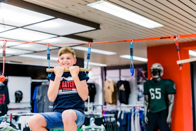 11Parcours im Sporthaus: Jugendlicher macht einen Klimmzug